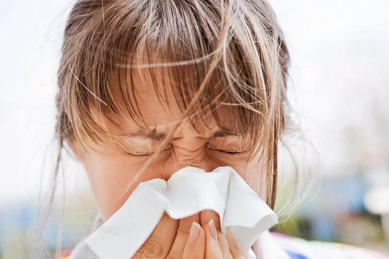 Woman with seasonal allergies sneezing
