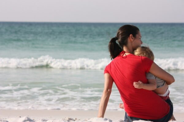 mom snuggling her son at the beach