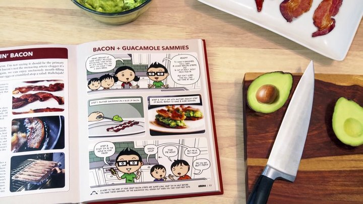 open cookbook beside a knife and a sliced avocado