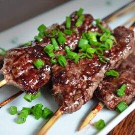 four smashed streak skewers on a plate topped with sliced green onion