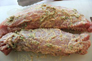 raw pork tenderloins seasoned and ready for cooking