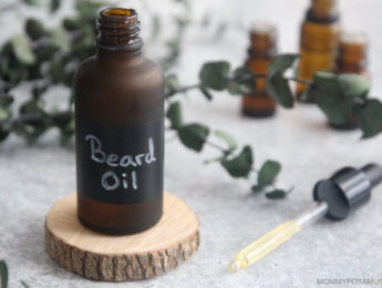 bottle of beard oil sitting on a round cut of wood