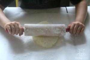 girl using rolling pin to flatten dough
