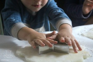 boy using cookie cutters to cut dough