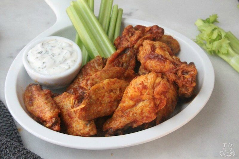 Crispy buffalo wings on plate with ranch dressing and celery sticks