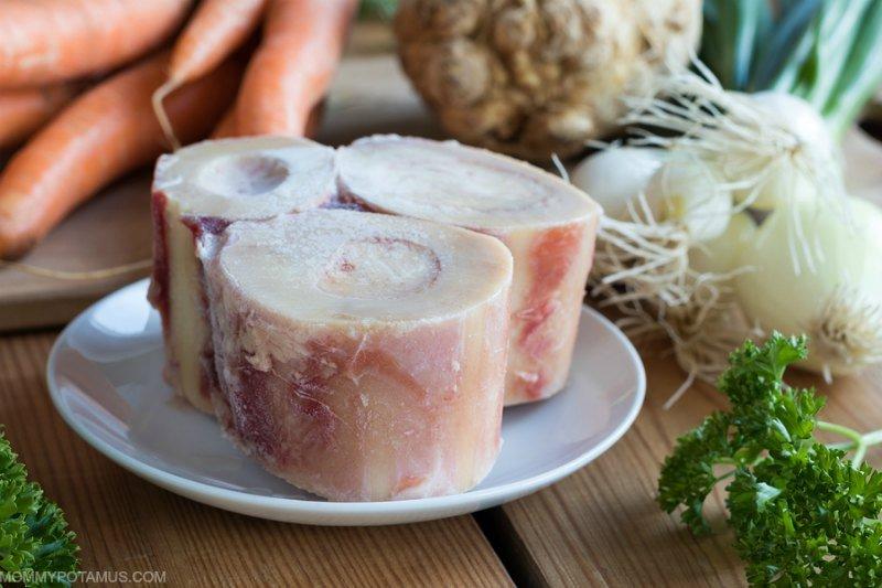 Ingredients for making bone broth on table: marrow bones and vegetables