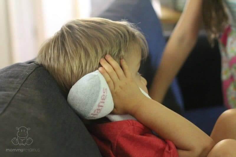 Child holding salt sock earache remedy over ear