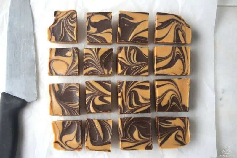 Peanut butter fudge with chocolate swirls on parchment paper, freshly cut into pieces