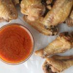 Crispy baked chicken wings on parchment paper with buffalo sauce