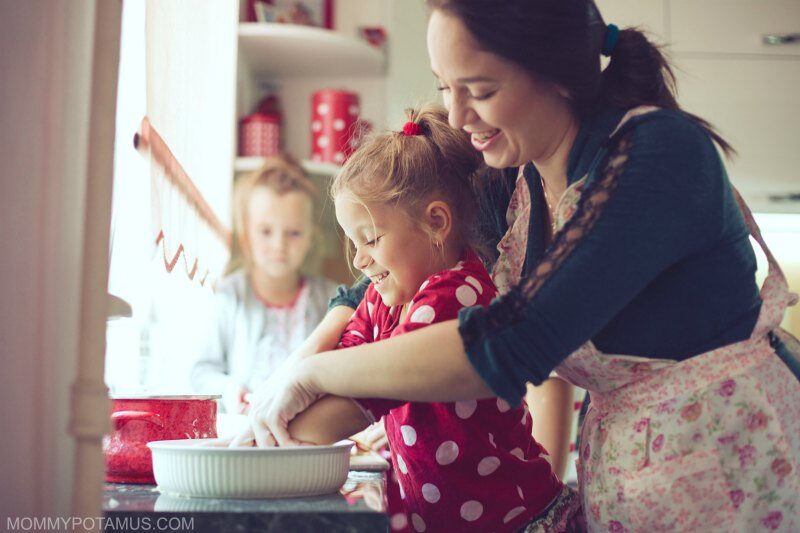 Mom and daughters baking together as part of holiday family tradition