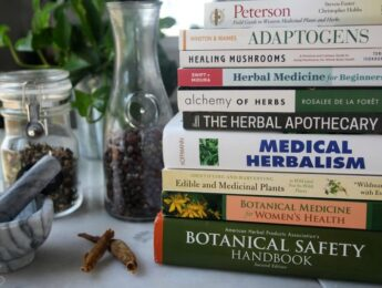 Stack of herbal books on table