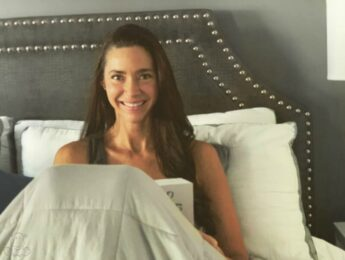 Woman sitting in bed with book and weighted blanket over her legs