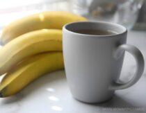 banana peel tea in a cup beside a bunch of bananas