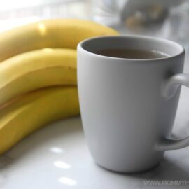 banana peel tea in a cup beside a bunch of bananas