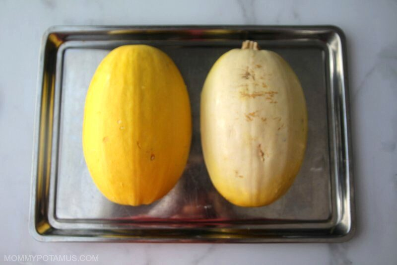 two halves of a spaghetti squash lying face down in a glass baking dish