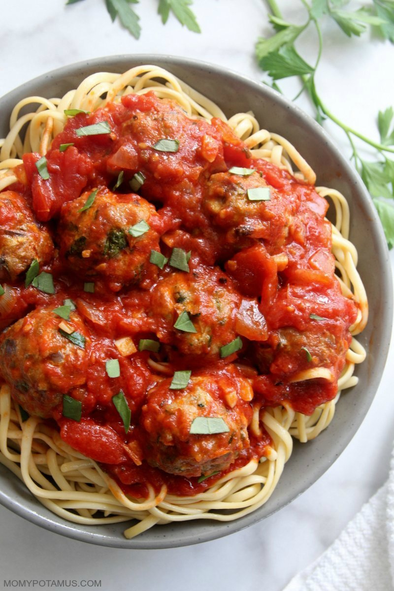 Overhead view of marinara sauce over meatballs