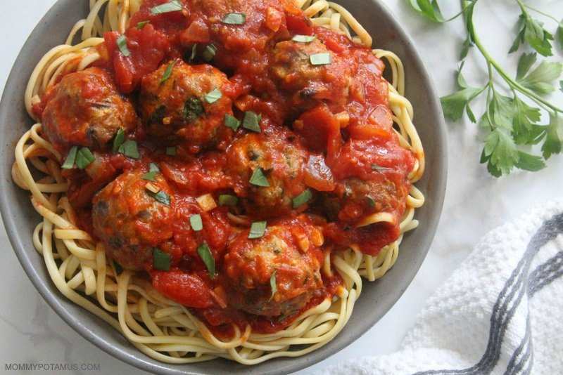 Homemade marinara sauce over meatballs and pasta in a bowl