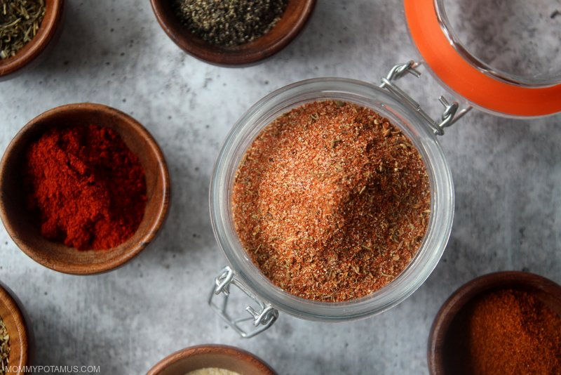 Homemade cajun seasoning in a jar surrounded by individual spices and herbs.