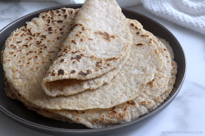 Stack of gluten-free tortillas on a plate with top one folded over.