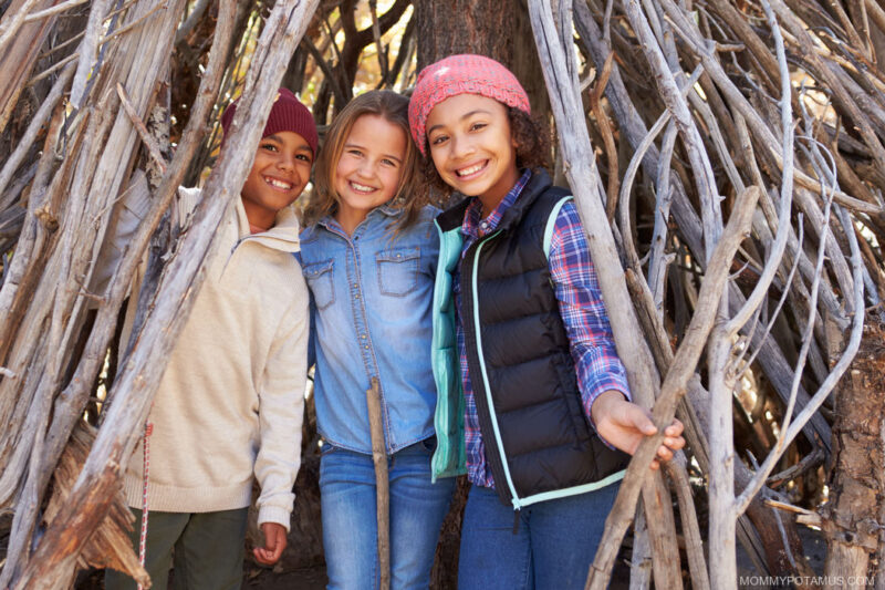 Young kids smiling inside homemade fort