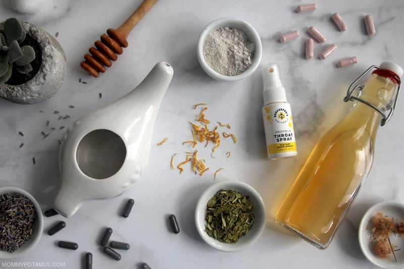 Overhead view of neti pot, activated charcoal, vitamin C, herbs and other home remedy essentials