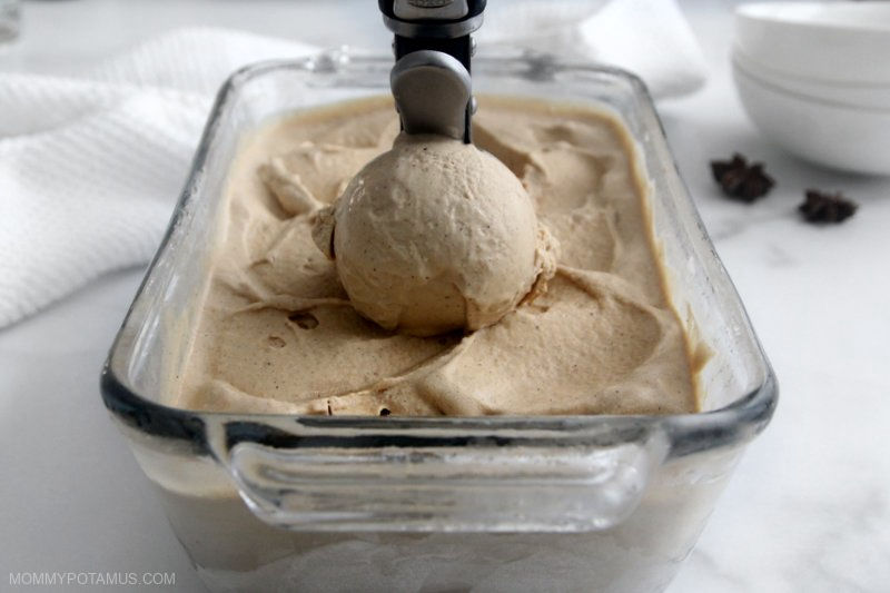 Front view of scooping chai ice cream out of container.