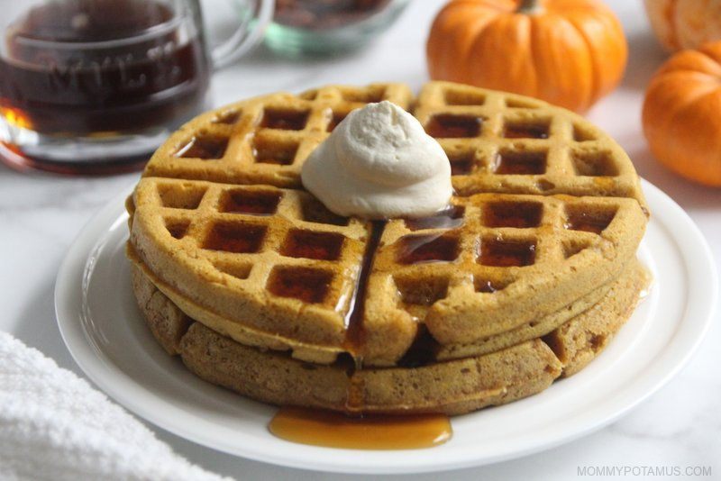 Pumpkin waffles on plate with maple syrup and whipped cream