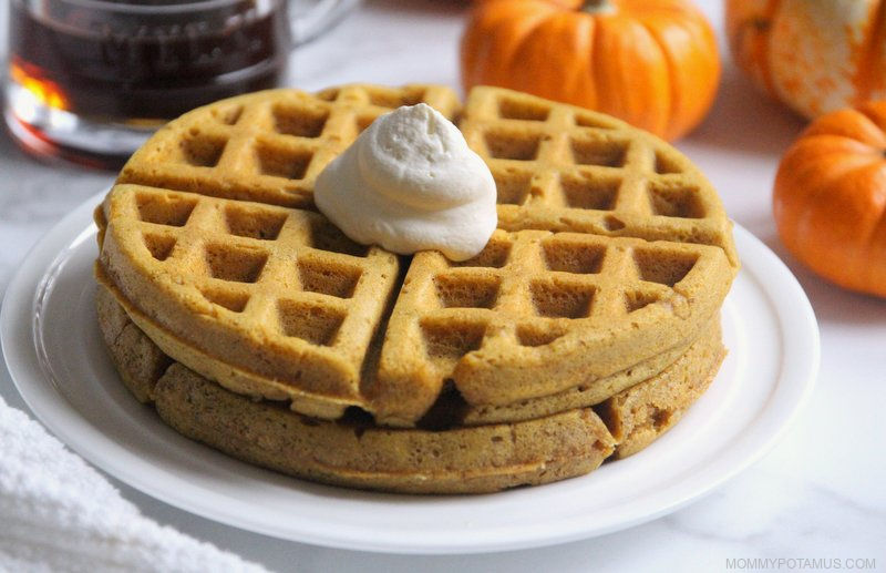 Pumpkin waffles on plate with a dollop of whipped cream