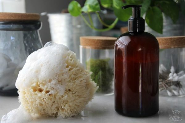 Homemade body wash on table with natural sponge and suds