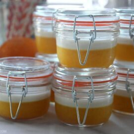 Jars of homemade gelatin cups on counter next to oranges