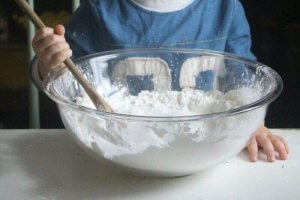 boy mixing the cornstarch in a mixing bowl