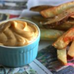 French fries on a table beside a ramekin of chipotle mayo