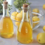 Bottles of homemade limoncello on counter with lemons